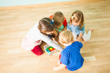 Four little siblings collecting toys in plastic box