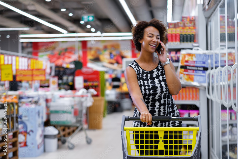 Fototapety, obrazy: Pretty black woman choosing goods in a grocery store