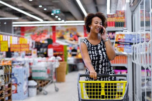 Pretty black woman choosing goods in a grocery store Fototapet