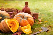 A Group Of Pumpkins And A Piece Of Pumpkin On Straw With A Cleaver, Ceramic Bottle And Mug In The Field.