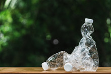 Plastic Bottle On Wooden In Nature Background. Global Warming Concept.