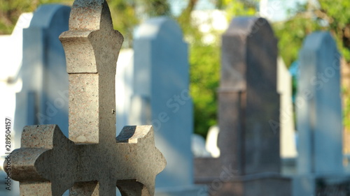 Photo cross with marble tombs in row