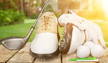 A Pair Of Golfing Shoes And A Golf Club On  Background