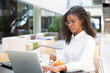 Serious young businesswoman having breakfast in cafe. Business woman drinking coffee and using laptop in coffee shop. Business morning concept