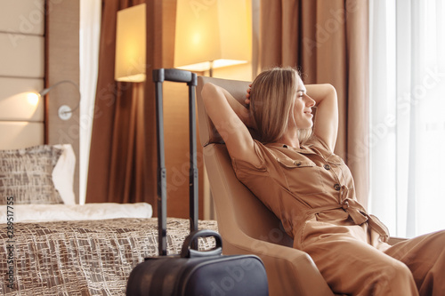 Stampa su Tela Satisfied smiling young beautiful American European woman relaxes in comfortable chair next to her suitcase while checking into hotel on vacation