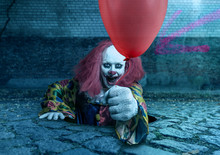 Scary Clown With A Balloon Rising From The Sewer