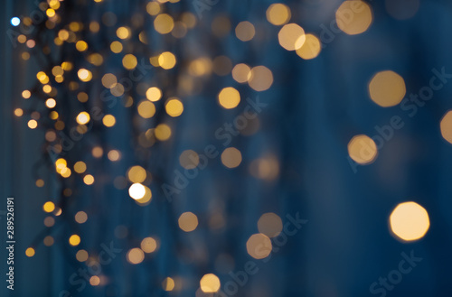 holiday, illumination and decoration concept - bokeh of christmas garland lights over dark blue background