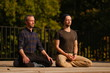 A yoga teacher and his student meditate while sitting in a lotus position on an open terrace. Outdoor yoga classes