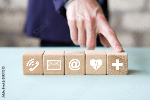 Fototapety, obrazy: CONTACT US concept. Man hand arranging wood block stacking with mail, phone, email icon. customer support concept insurance for your health.