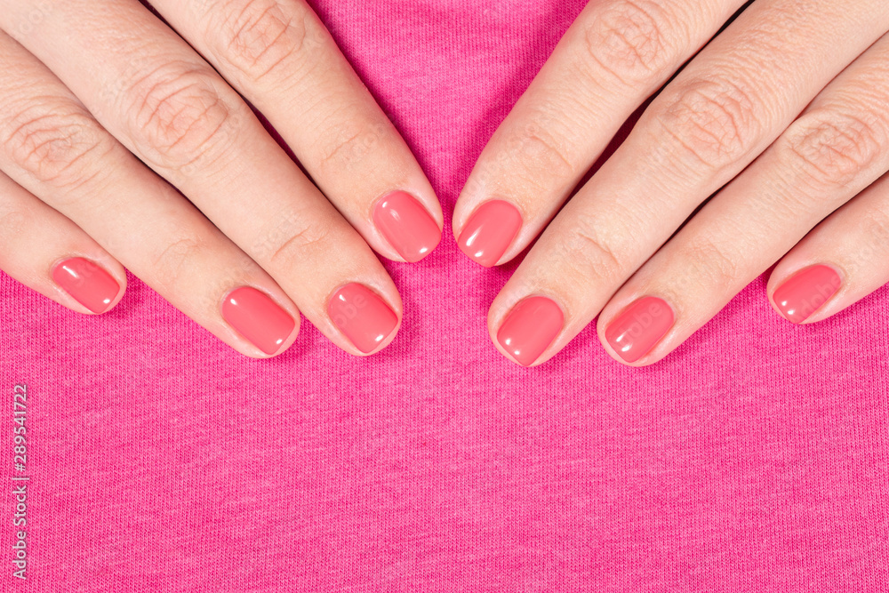 Fototapeta Closeup top view of female fingers manicured with bright pink gel polish isolated on pink fabric texture background. Horizontal color photography.