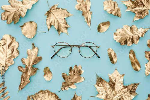 top view of autumnal golden foliage and glasses on blue background