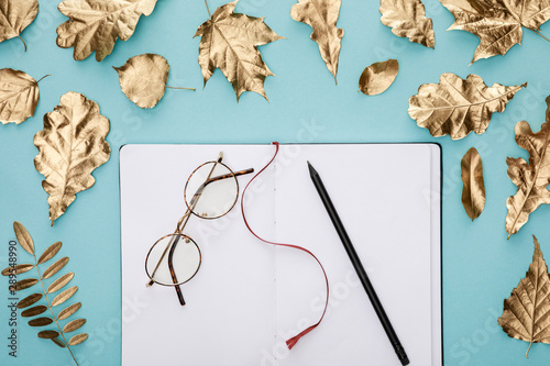 top view of autumnal golden foliage near blank notebook with glasses on blue background