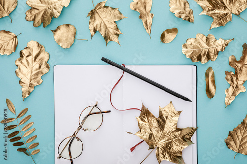 top view of autumnal golden leaves near blank notebook with glasses on blue background