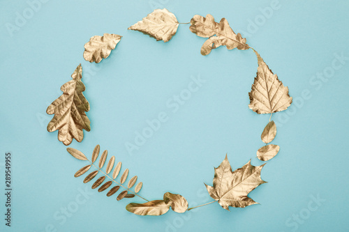 round frame of autumnal golden foliage on blue background with copy space