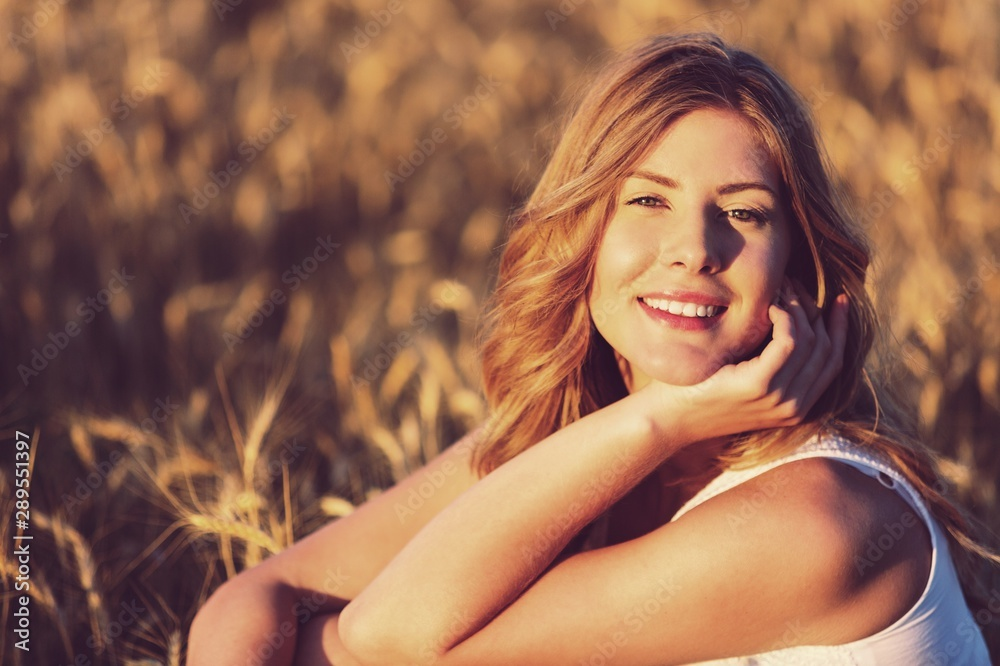 Fototapety, obrazy: Young woman on field under sunset light