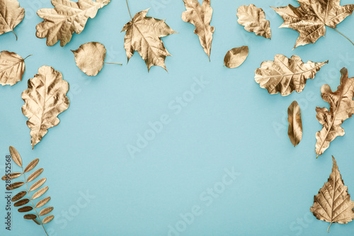 top view of autumnal golden leaves on blue background
