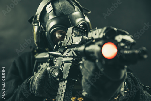 Photo Elite special unit soldier with gasmask is holding assault rifle and aiming at t