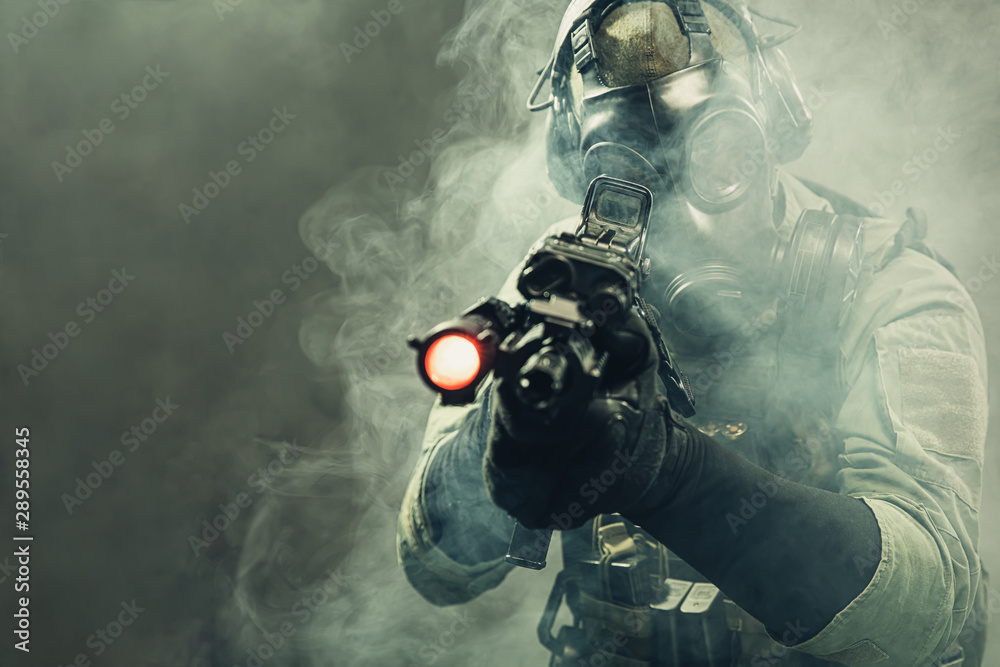 Fototapeta Special force soldier with gasmask between smoke at battlefield is aiming the target