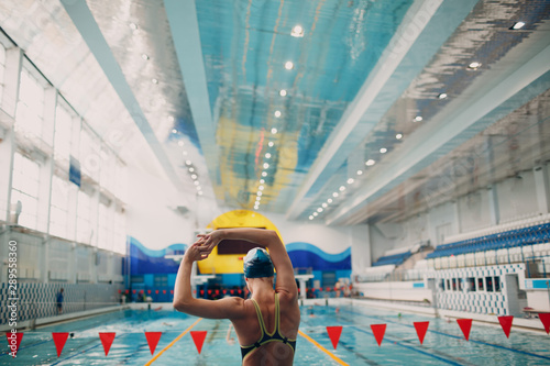Fototapeta  Young woman swimmer warming up before swim in swimming pool