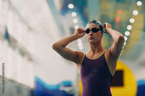 Fotografía  Young woman swimmer getting ready for competition and swim in swimming pool