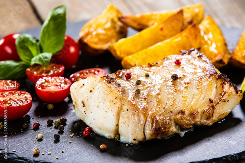 Fototapeta  Fried cod loin with baked potatoes and vegetables