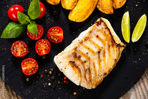 Fried cod loin with baked potatoes and vegetables - 289558933