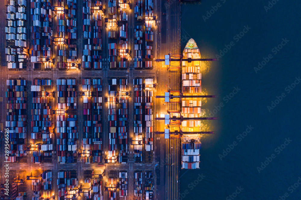 Fototapety, obrazy: Aerial top view of container cargo ship in the export and import business and logistics international goods in urban city. Shipping to the harbor by crane in Victoria Harbour, Hong Kong City at night.