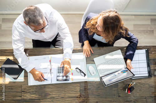 Businesspeople Using Laptop In Office Canvas Print