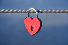 A Red Padlock In A Heart Form Of A Heart Hanging On A Bridge Railing On The Background Of A River