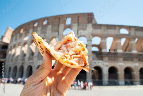 Obraz na plátne  Hand Holding Italian Pizza Near Colosseum