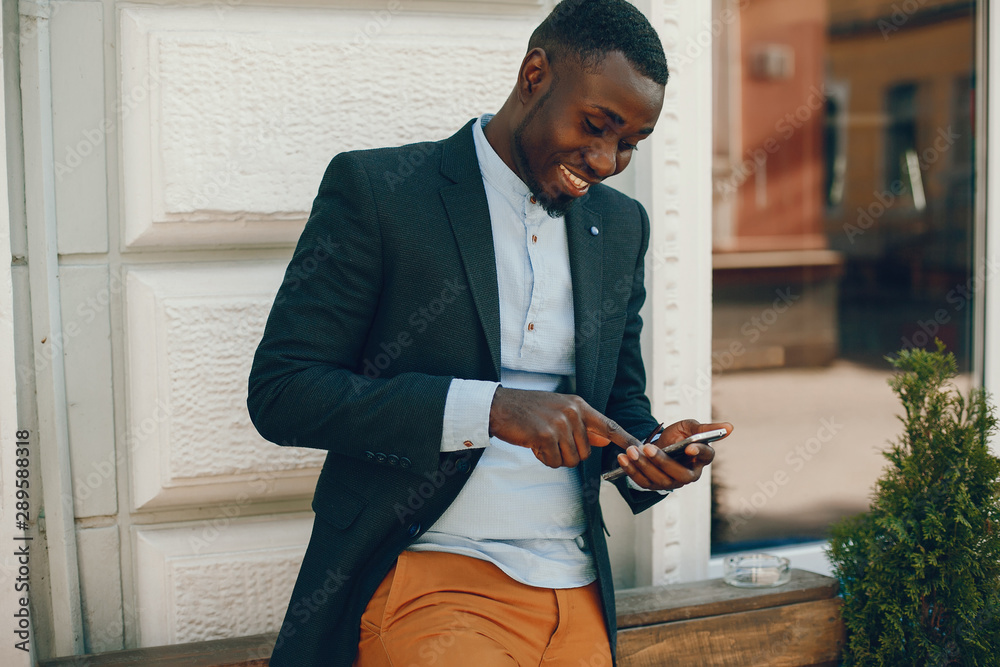 Fototapeta elegant and stylish black guy in a blue shirt and black jacket standing in the summer city