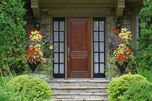 Wooden Front Door Of Old Stone House With Flowers And  Cedar Bushes