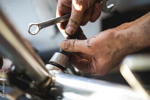 Fixing the bicycle problem in workshop stock photo - 289594532