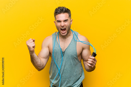 Caucasian man holding a jump rope cheering carefree and excited Wallpaper Mural
