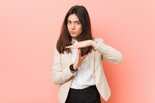 Young Brunette Business Woman Against A Pink Background Showing A Timeout Gesture.