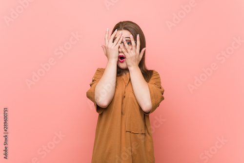 Obraz na plátně  Young student woman wearing eyeglasses blink through fingers frightened and nervous