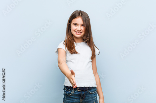 Cute girl stretching hand at camera in greeting gesture.