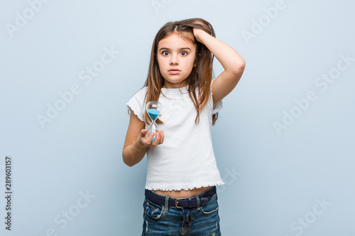 Fotografie, Tablou Little caucasian girl holding an hourglass being shocked, she has remembered important meeting
