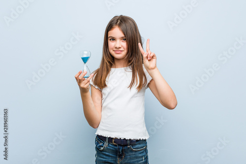 Fototapeta Little caucasian girl holding an hourglass showing number two with fingers. obraz