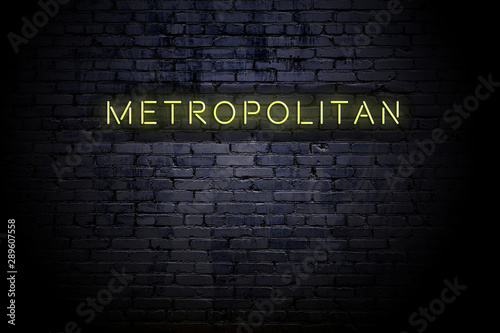 Highlighted brick wall with neon inscription metropolitan Wallpaper Mural