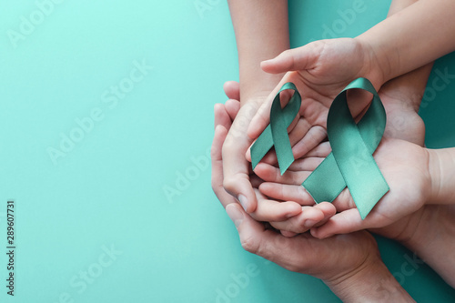 Adult and children hands holding Teal ribbons on blue background, Ovarian Cancer Wallpaper Mural