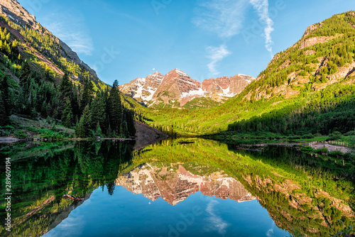 Fototapeta Maroon Bells lake at sunrise panoramic view in Aspen, Colorado with rocky mountain peak and snow in July 2019 summer and vibrant light reflection on water obraz