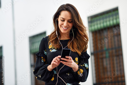 Photographie  Woman listening to the music with earphones and smart phone outdoors