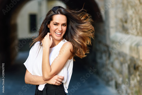 Papel de parede  Young woman moving her long hair in urban background.