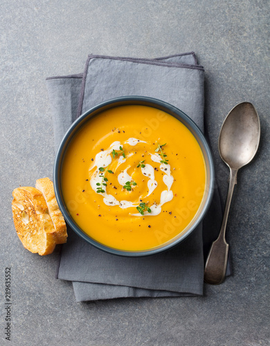 Pumpkin, carrot cream soup in a bowl. Grey background. Top view. Canvas Print