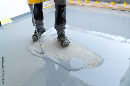 Valokuva  construction worker renovates balcony floor and pours watertight resin and glue