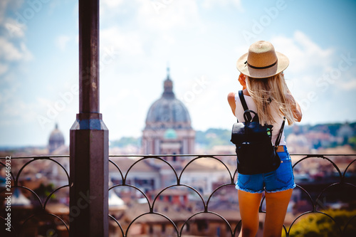 Obraz Rome Europe Italia travel summer tourism holiday vacation background -young smiling girl with mobile phone camera and map in hand standing on the hill looking on the cathedral Vatican - fototapety do salonu