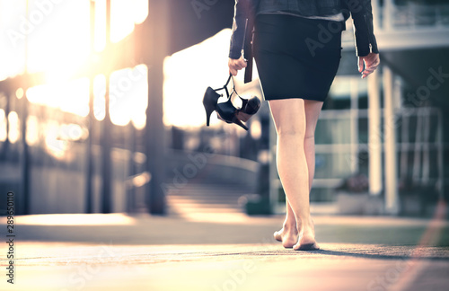 Cuadros en Lienzo Woman holding high heels in hand and walking home from party barefoot
