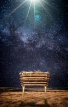 Vertical Shot Of An Old Wooden Cradle With Hay In A Field And Under A Beautiful Starry Sky