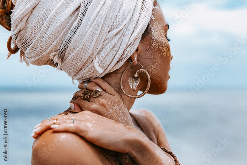 close up of beautiful young tribal woman in turban at blue sea and sky backgroun Canvas Print